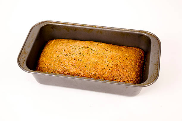 fresh zucchini bread in pan on white background stock photo
