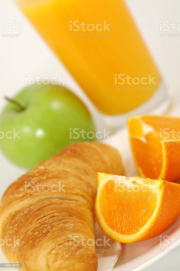 Fresh-baked croissant, green apple, orange juice and wedges royalty-free stock photo