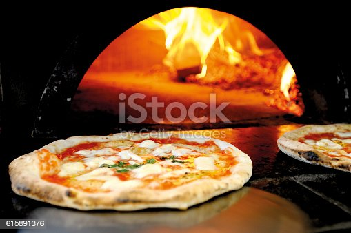 A just cooked italian pizza in front of a wood oven.