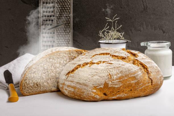 Freshly baked artisan sourdough bread with sourdough starter on a kitchen countertop stock photo