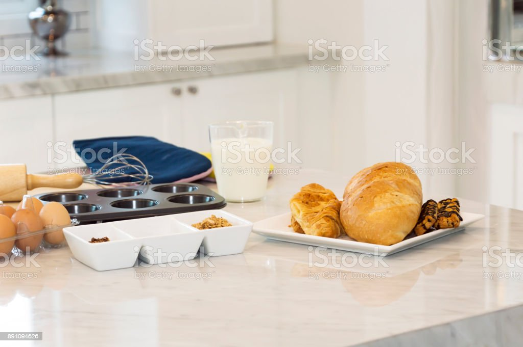 Freshly baked baguette and bread with ingredients for whole grain healthy bread,Granola and milk and eggs in the kitchen. stock photo