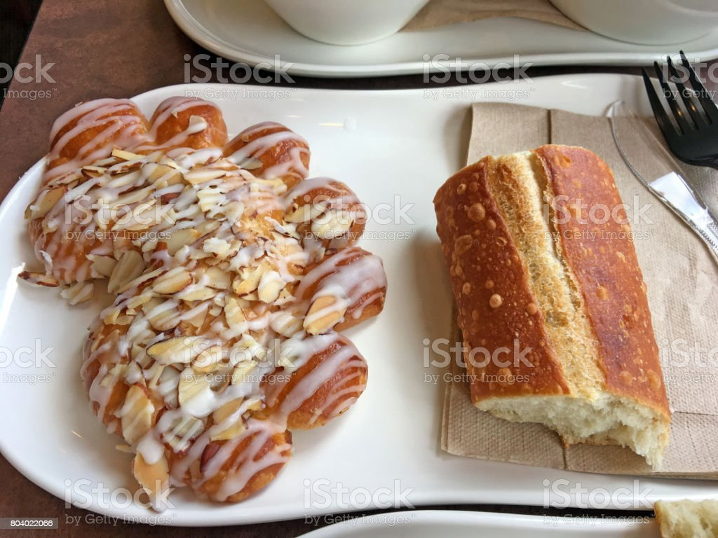 Freshly baked bearclaw pastry and French bread on a white plate stock photo