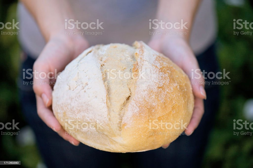 Freshly baked bread in woman's hands stock photo