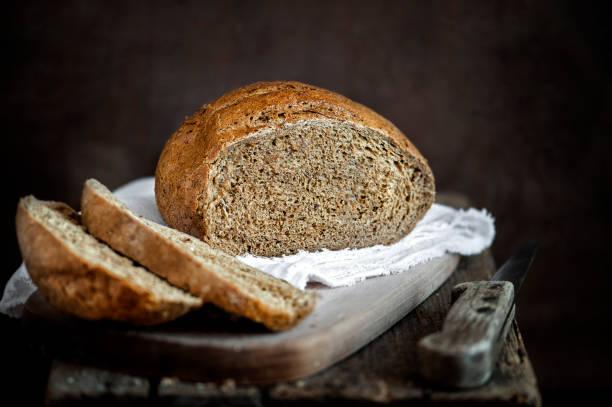 pan recién horneado sobre un fondo rústico - pan multicereales fotografías e imágenes de stock