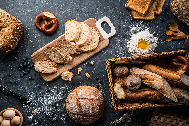 freshly baked bread on wooden table - bakery stockfoto's en -beelden