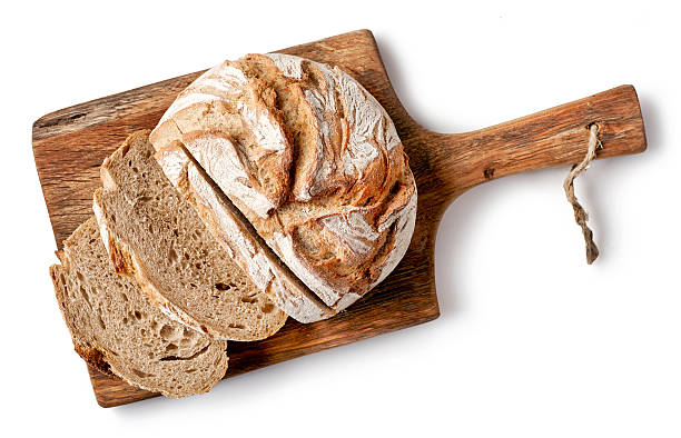 freshly baked bread freshly baked bread on wooden cutting board isolated on white background, top view bread stock pictures, royalty-free photos & images