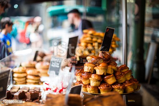 Close up horizontal color image depicting a selection of freshly baked delicious cakes and pastries for sale at Borough Market in London, one of the oldest and most popular food markets in the world. People and customers are blurred out of focus in the background. Room for copy space.