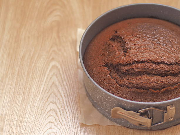 freshly baked chocolate cake in baking pan upon wooden background - schokoladen biskuitkuchen stock-fotos und bilder
