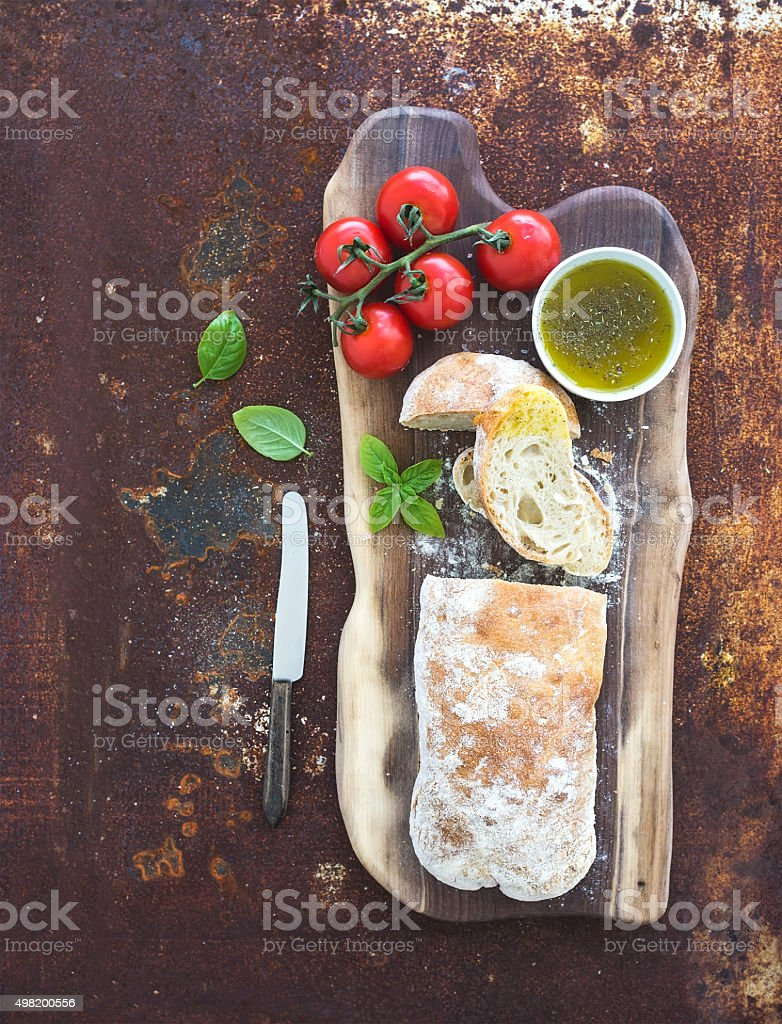 Freshly baked ciabatta bread with cherry-tomatoes, olive oil, basil stock photo