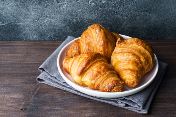 Freshly baked croissants on a plate, dark background, copy space. Freshly baked croissants on a plate, dark background, copy space. croissant stock pictures, royalty-free photos & images