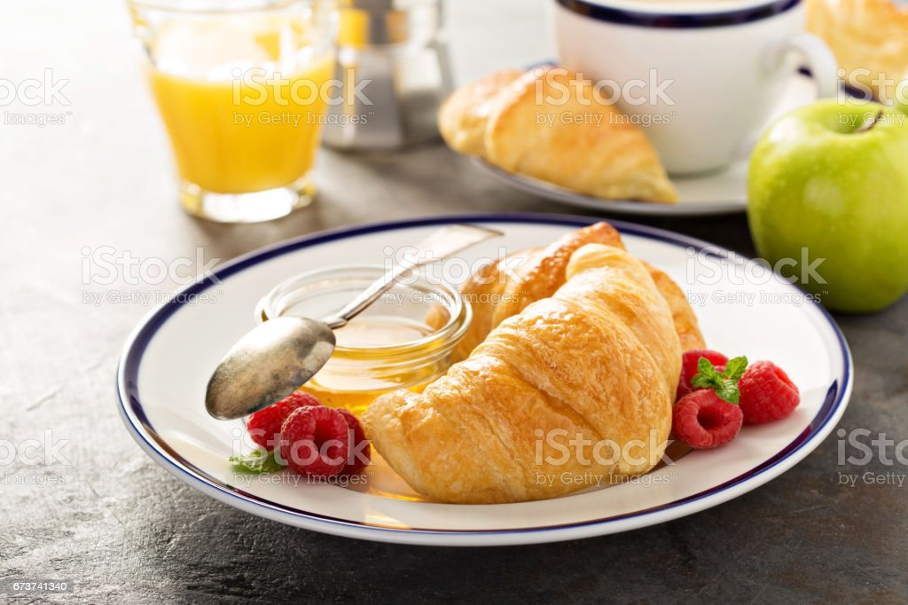 Freshly baked croissants with honey and jam royalty-free stock photo