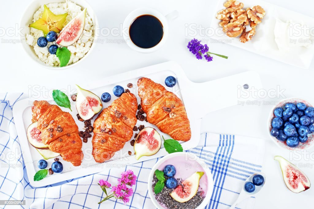 Freshly baked croissants, yogurt with chia and blueberry, ricotta with starfruit and cup of black coffee on white table. stock photo