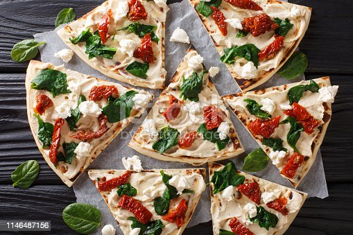 Freshly baked flatbread with hummus, sun-dried tomatoes, spinach and goat cheese close-up on the table. Horizontal top view from above