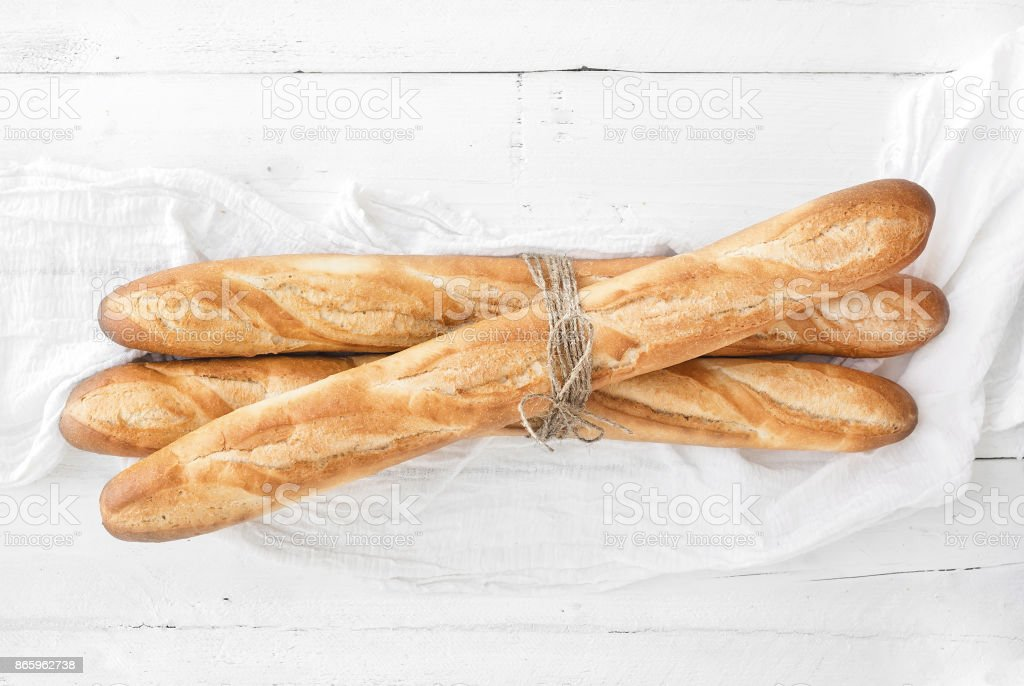 Freshly baked French baguettes on white wooden table stock photo