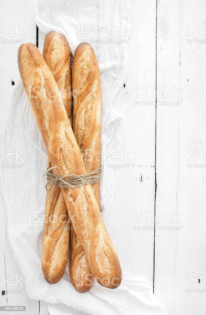 Freshly baked French baguettes on white wooden table. Top view stock photo