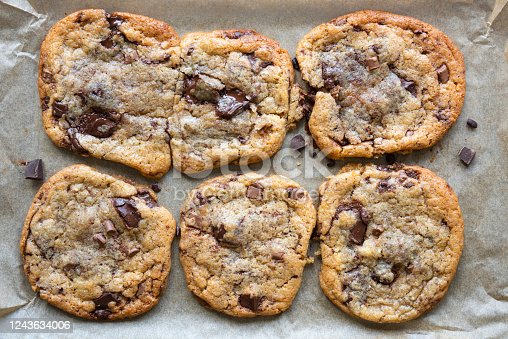 A flat baking sheet lined with greaseproof paper holds six freshly baked chocolate chip cookies. The chocolate in the cookies has melted leaving the biscuits gooey. There are chocolate smears and stray chocolate chips on the tray around the cookies.