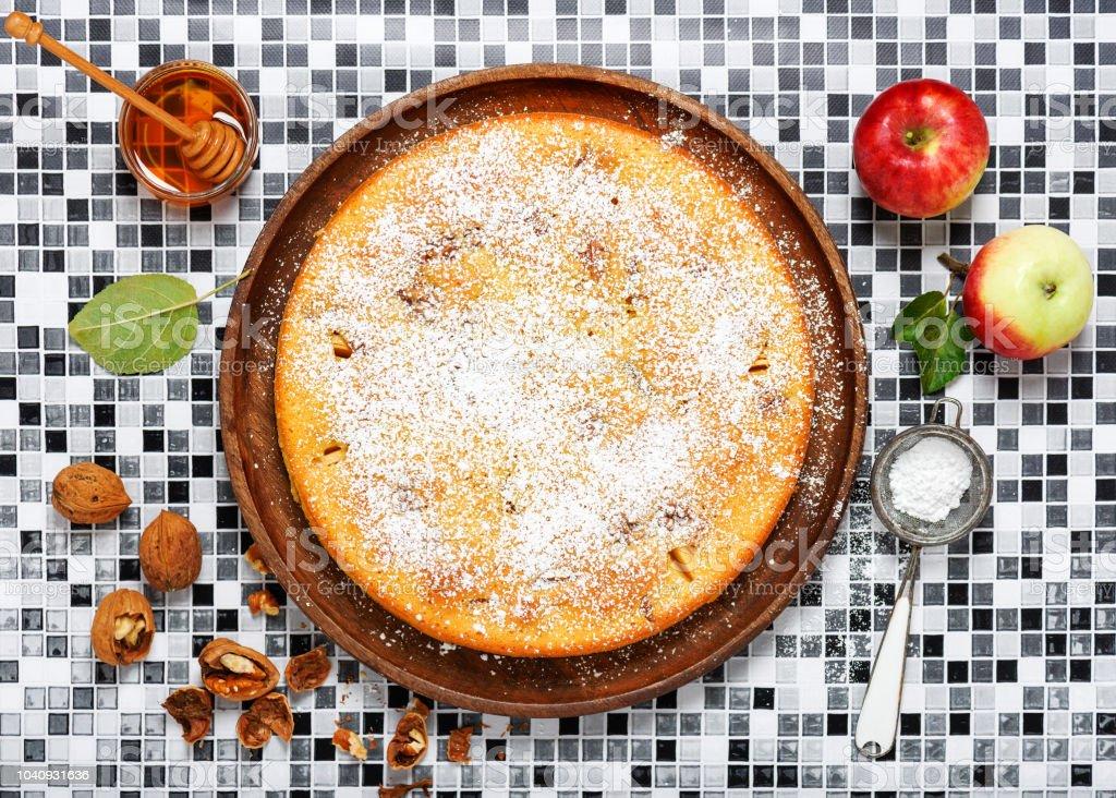Bolo de noz recém-assados maçã caseiro, polvilhado com açúcar de confeiteiro sobre uma placa de madeira. - foto de acervo