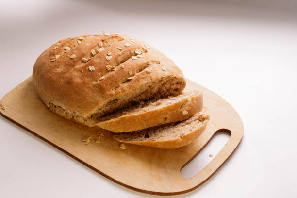 Freshly baked homemade buckwheat flour and whole grain corn bread. Bread sprinkled with oat flakes on a white background. Healthy gluten free food. stock photo