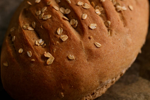 Freshly baked homemade buckwheat flour and whole grain corn bread. Bread sprinkled with oat flakes on a dark background. Healthy gluten free food. stock photo