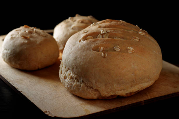 Freshly baked homemade buckwheat flour and whole grain corn bread. Bread sprinkled with oat flakes on a dark background. Healthy gluten free food. Low key photo stock photo