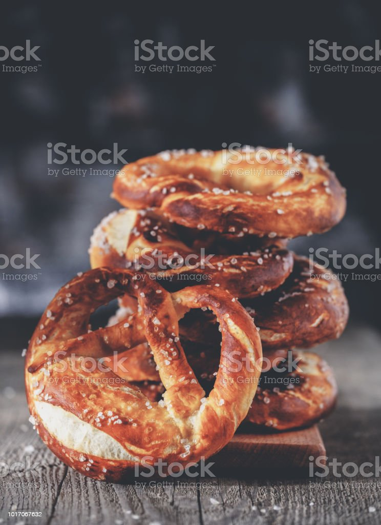 Freshly baked homemade soft pretzel with salt on rustic wooden table стоковое фото