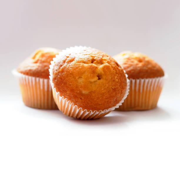 frisch gebackene muffins. drei muffins in wachs-liner auf hellem hintergrund. kleiner keks leckere cupcakes, lecker - vanille muffins stock-fotos und bilder