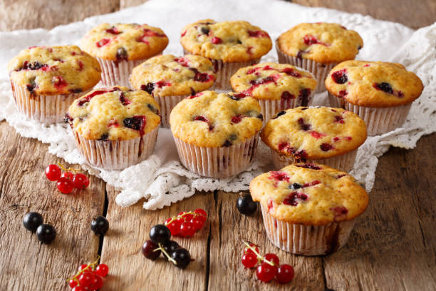 Freshly baked muffins with black and red currant berries close-up. horizontal stock photo