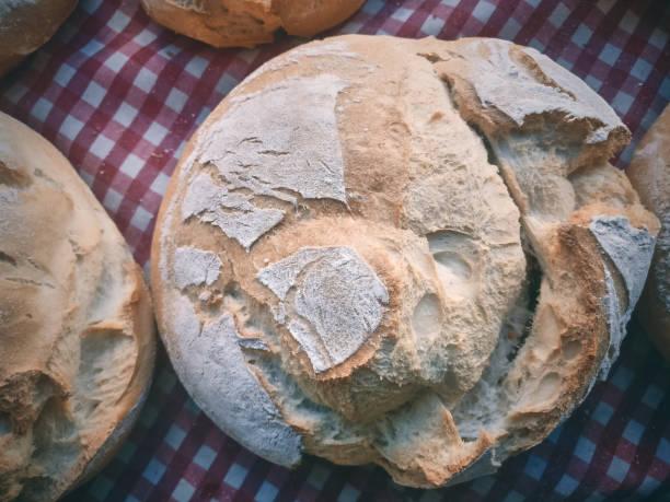 frisch gebackenes naturbrot auf einem weiß und rot karierten tischtuch, von oben betrachtet - kochen mit oliver stock-fotos und bilder