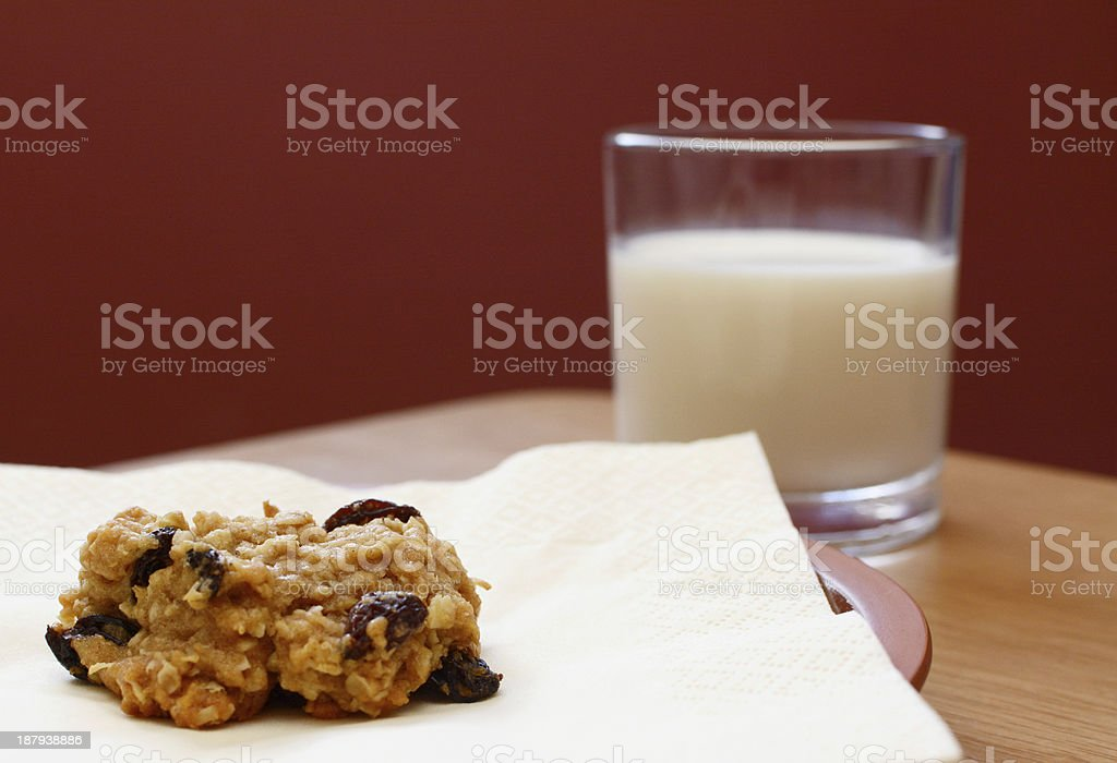 Freshly baked oatmeal raisin cookie with a glass of milk stock photo