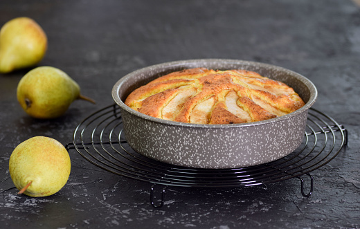 Freshly baked pear cake in a baking dish on a black background.