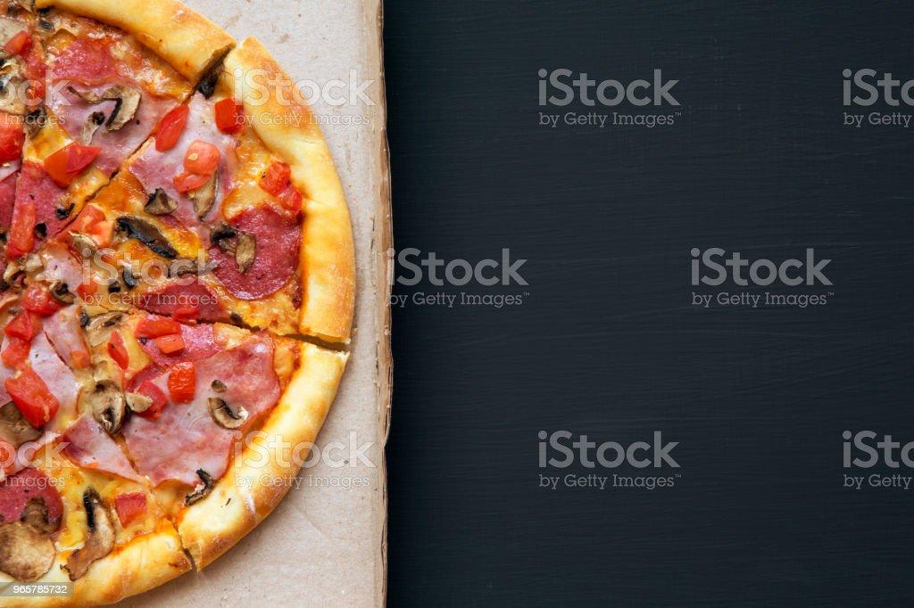 Versgebakken pizza in een kartonnen doos op een donkere achtergrond, bovenaanzicht. Close-up, kopie ruimte. Vlakke lay, van bovenaf. - Royalty-free Avondmaaltijd Stockfoto