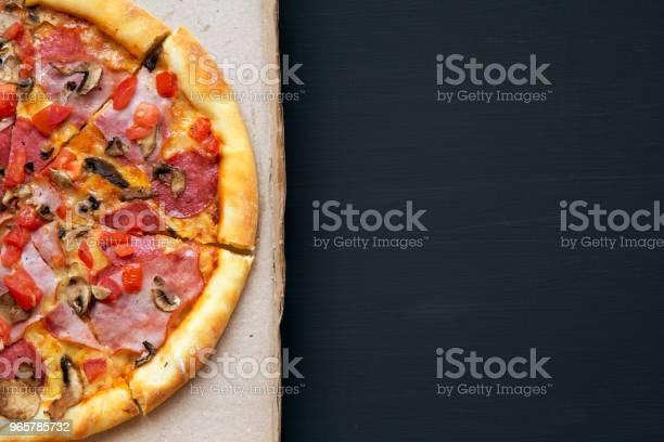 Versgebakken Pizza In Een Kartonnen Doos Op Een Donkere Achtergrond Bovenaanzicht Closeup Kopie Ruimte Vlakke Lay Van Bovenaf Stockfoto en meer beelden van Avondmaaltijd