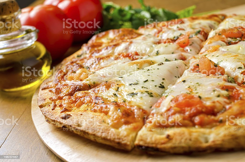 Freshly baked pizza margherita on a wooden board royalty-free stock photo