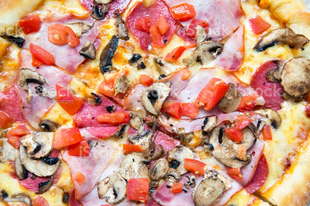 Freshly baked pizza with bacon, tomatoes, salami, cheese and mushrooms, closeup. Top view. - Royalty-free Bacon Stock Photo