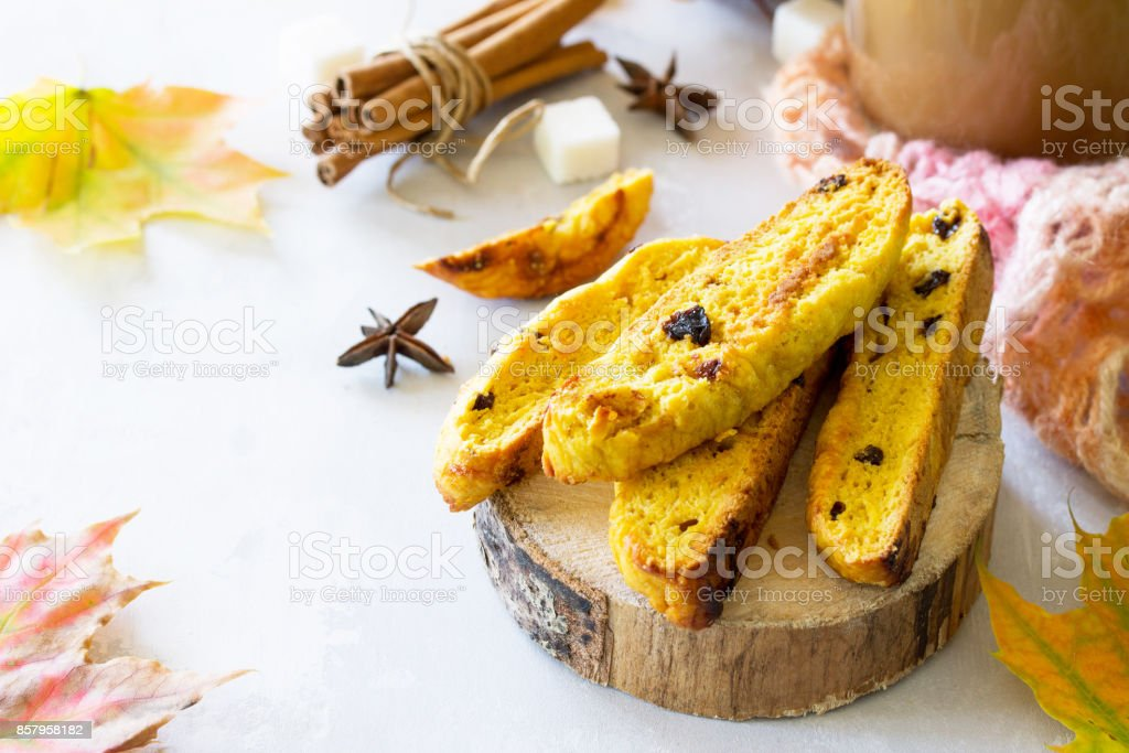 Freshly baked raisins and cinnamon biscotti and a cup of cappuccino coffee on a gray slate or slate background. stock photo