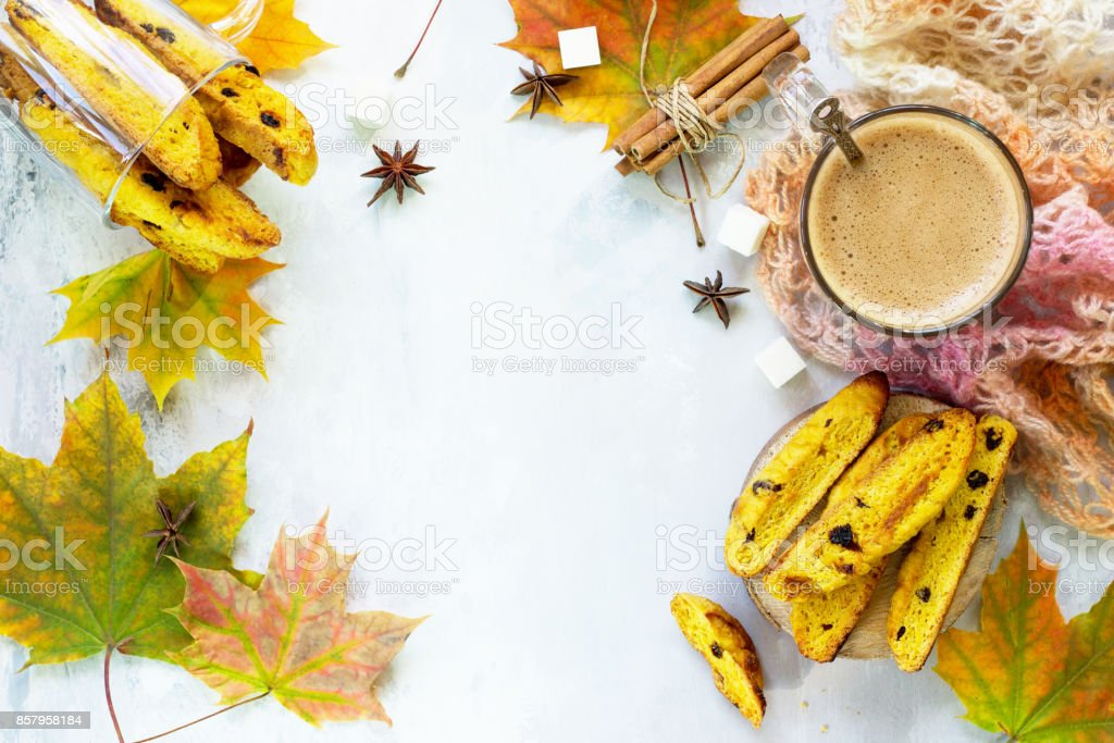 Freshly baked raisins and cinnamon biscotti and a cup of cappuccino coffee on a gray slate or slate background. Top view with copy space. stock photo