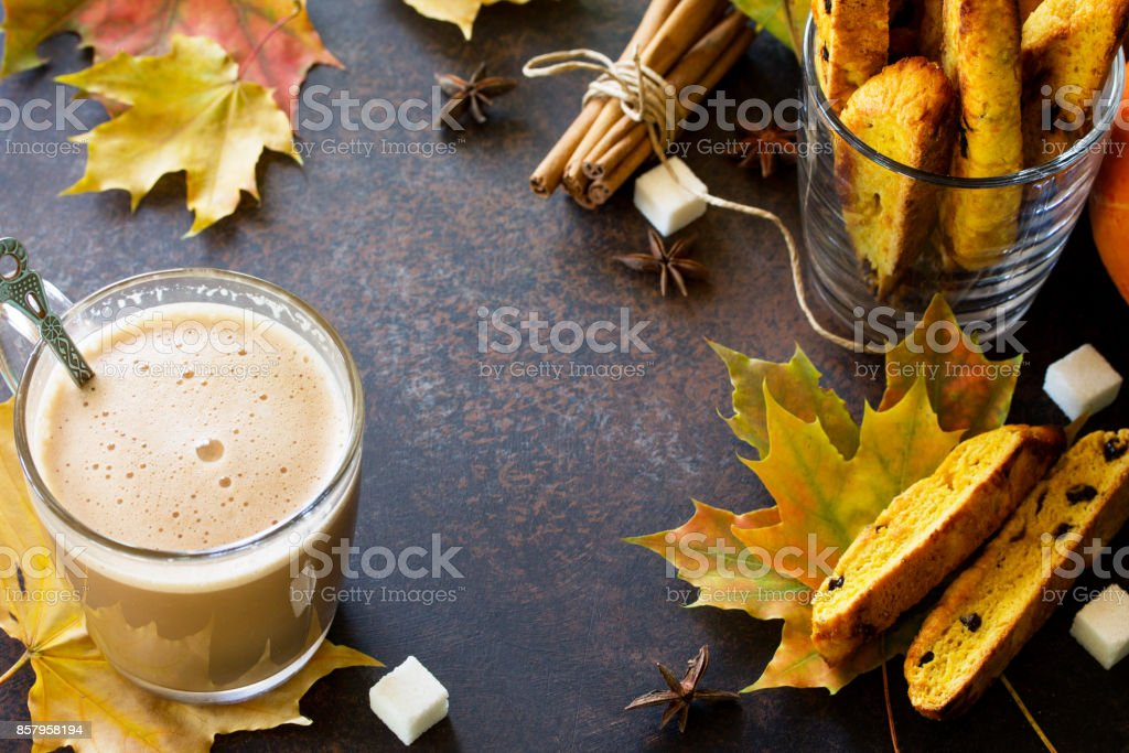 Freshly baked raisins and cinnamon biscotti and a cup of cappuccino coffee on a brown slate or slate background. stock photo