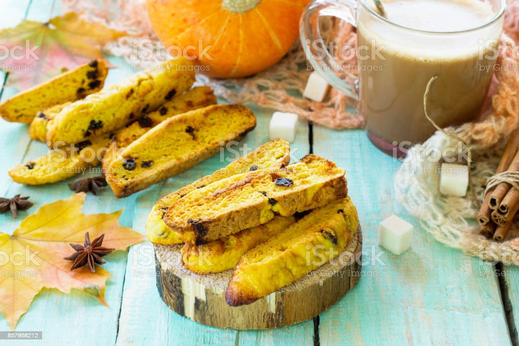 Freshly baked raisins and cinnamon biscotti and a cup of cappuccino coffee on a kitchen wooden table. stock photo