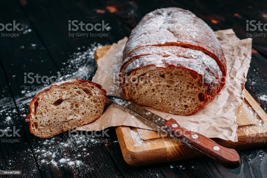 Freshly baked sliced rye bread on wooden cutting board stock photo