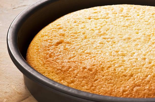 frisch gebackene rührkuchen in a round backen tin - biskuitboden stock-fotos und bilder