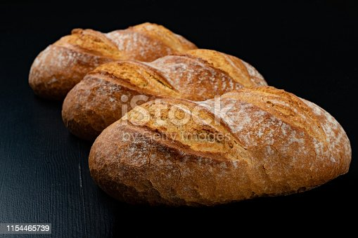 istock Freshly baked tasty bread on a dark table. Tasty baked goods straight from the bakery. Black background. 1154465739