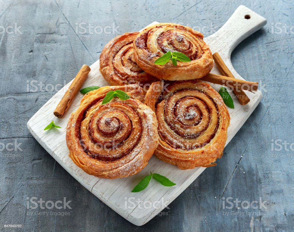 Freshly Baked Traditional Sweet Cinnamon Rolls, Swirl on white wooden board stock photo