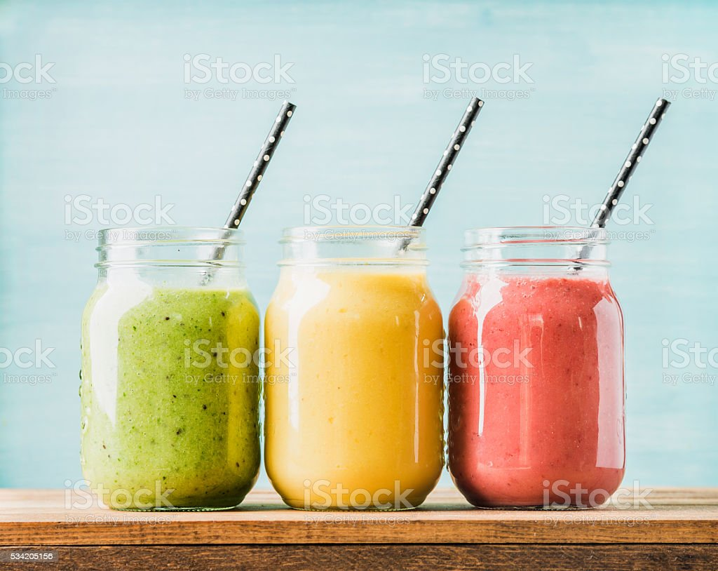 Freshly blended fruit smoothies of various colors and tastes in glass...