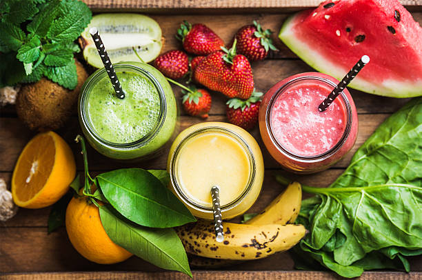 freshly blended fruit smoothies of various colors and tastes - milkshake stockfoto's en -beelden