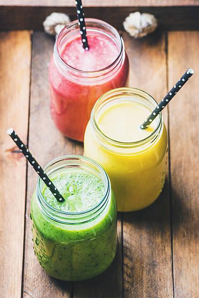 frische gemischte früchte-smoothies mit verschiedenen farben und aromen - einmachglassmoothie stock-fotos und bilder