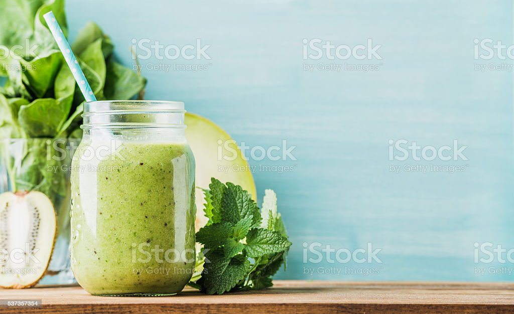 Freshly blended green fruit smoothie in glass jar with straw....