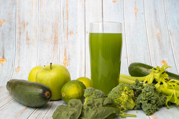 Freshly blended green smoothie in a glass on wooden background. Template for detox recipe, copy space. stock photo