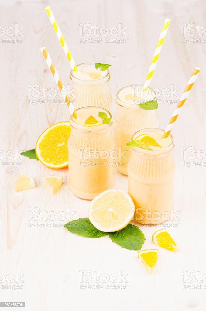 Freshly blended orange and yellow lemon smoothie in glass jars with straw, mint leaf foto de stock royalty-free