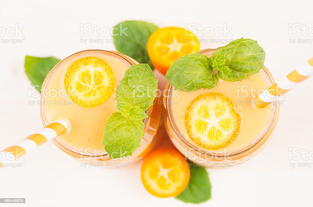 Freshly blended orange citrus kumquat  fruit smoothie in glass jars with straw, mint leaf, cute ripe berry, top view, close up. White wooden board background. foto de stock royalty-free