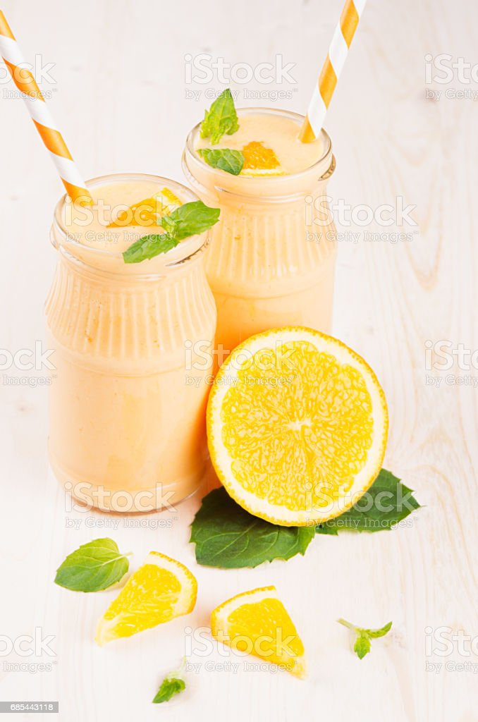 Freshly blended orange citrus smoothie in glass jars with straw, mint leaf, cut orange,  close up. White wooden board background. foto de stock royalty-free